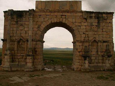 Vítězný oblouk - Vítězný oblouk, tyčící se ve středu měl především ceremoniální funkci vzhledem k hlavní ulici Decumanus Maximus. Byl vztyčen městskou radou mezi prosincem roku 216 a dubnem 217 na počest císaře Caracally Severa, který věnoval občanům Volubilisu římské občanství a zbavil je placení daní. (nahrál: Petr Kubík)